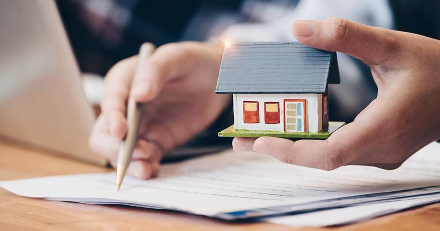 Image of person holding a house while reviewing bills